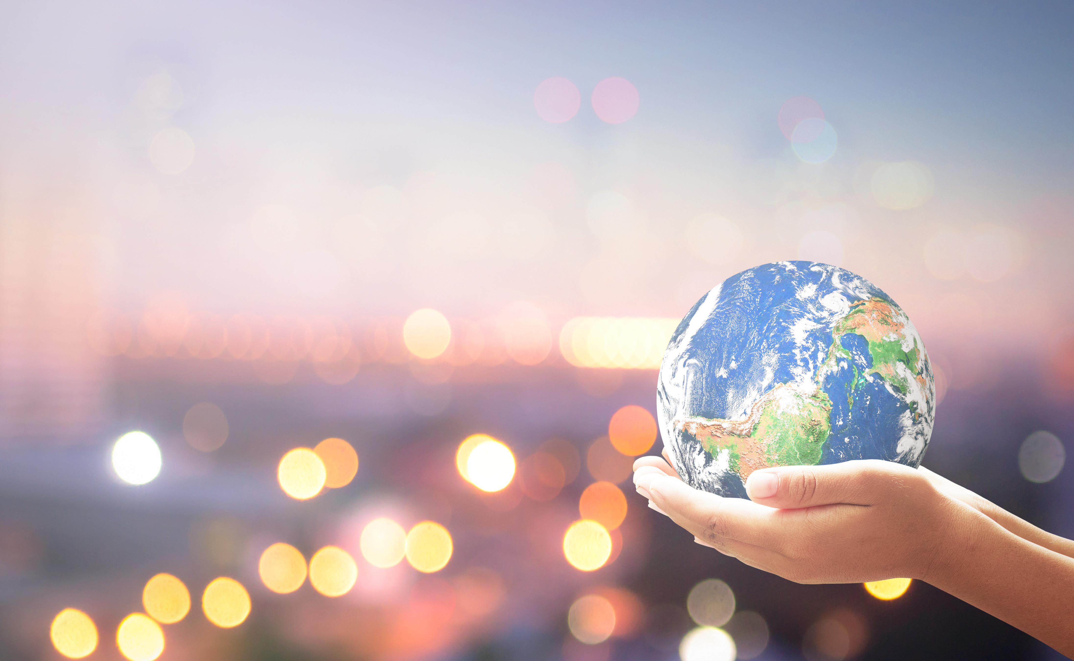 World environment day concept: Human hands holding earth globe over blurred city background. Elements of this image furnished by NASA
