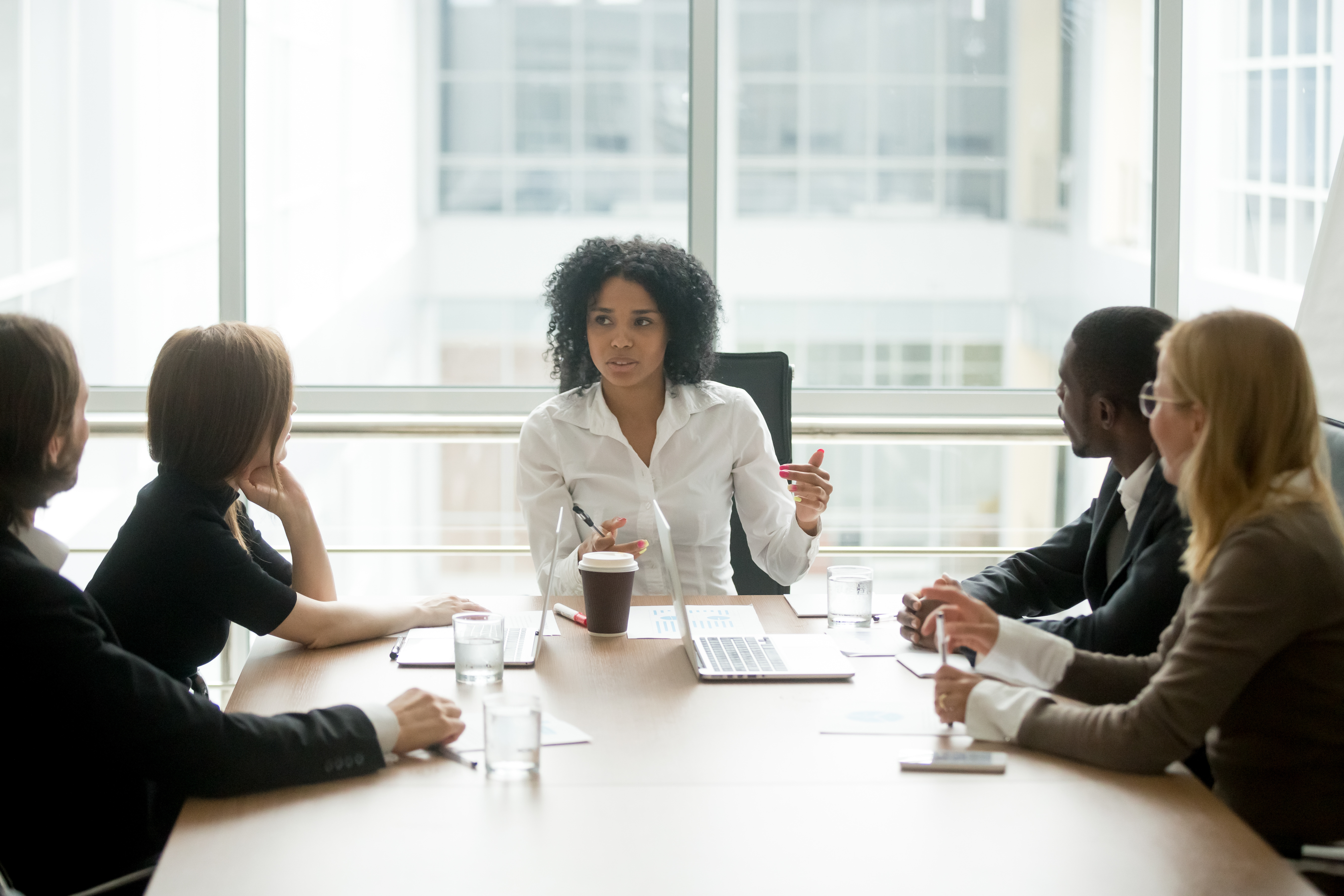 Black female boss leading corporate multiracial team meeting talking to diverse business people, african american woman executive discussing project plan at group multi-ethnic briefing in boardroom.