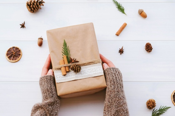 Wrapped gift box with natural decorations on white rustic wooden background. Zero waste.