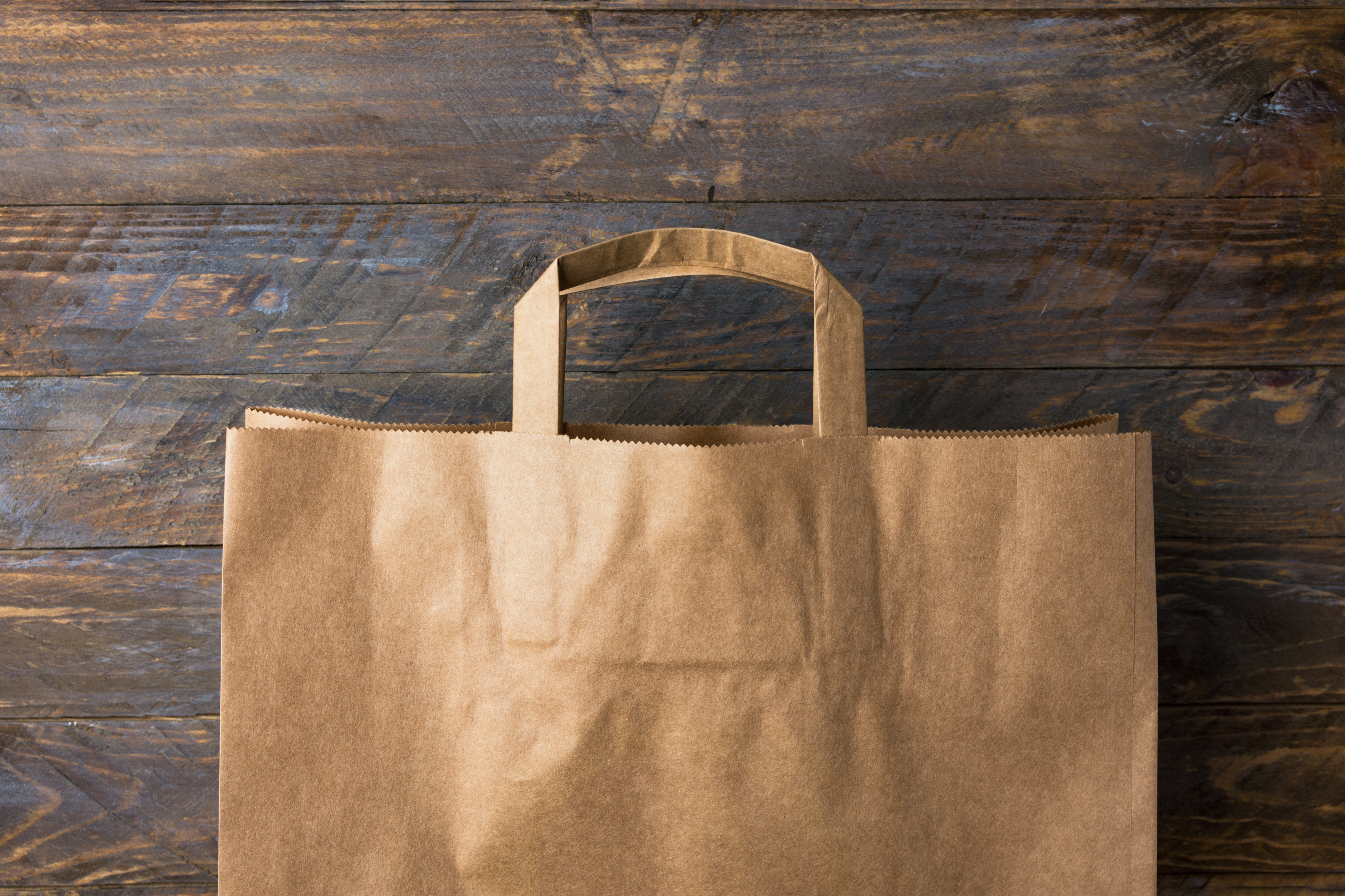 Brown kraft paper grocery shopping bag on wooden background. Plastic-free alternatives zero waste environmental protection nature friendly living.